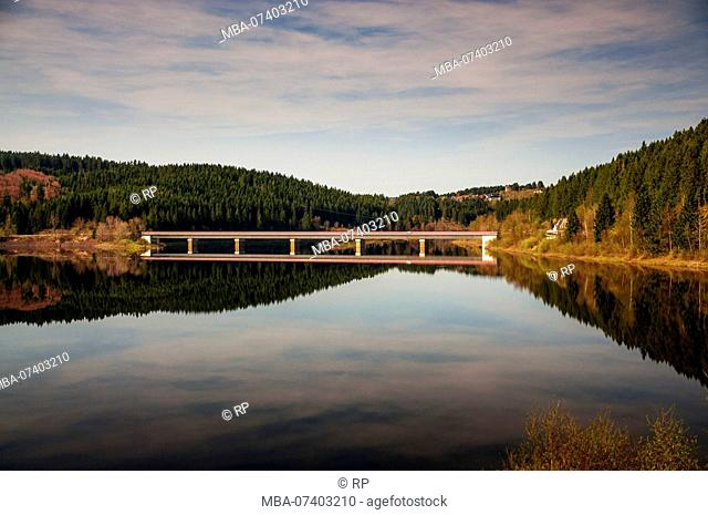 Bridge road over a mountain lake oker dam with perfect water reflections. Okertalsperre, Okerstausee, National Park Harz in Germany