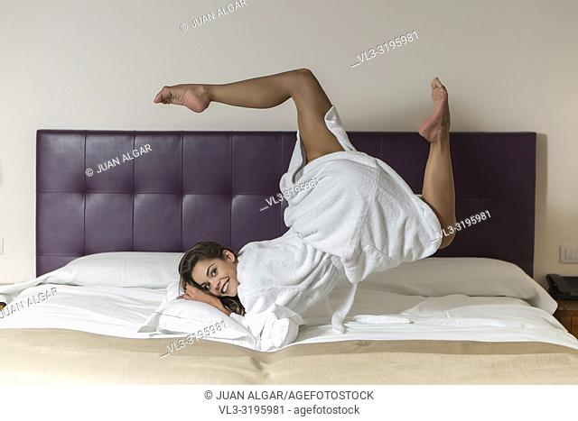 Attractive young female in white bathrobe rolling in bed in hotel room