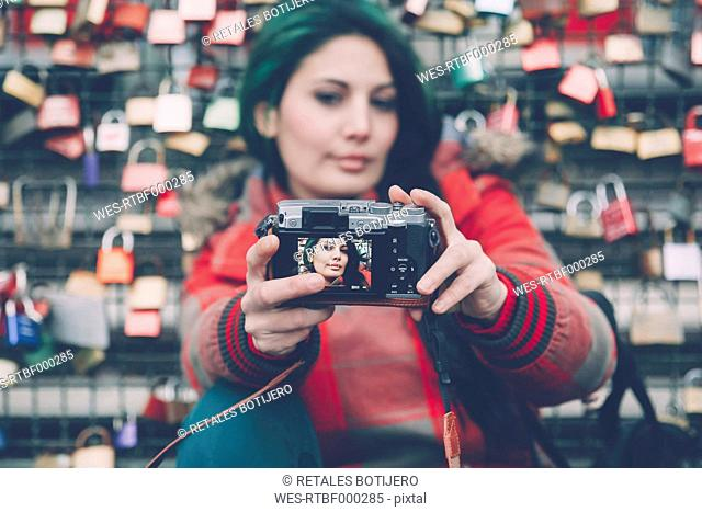 Germany, Cologne, woman taking selfie in front of love locks at Hohenzollern Bridge