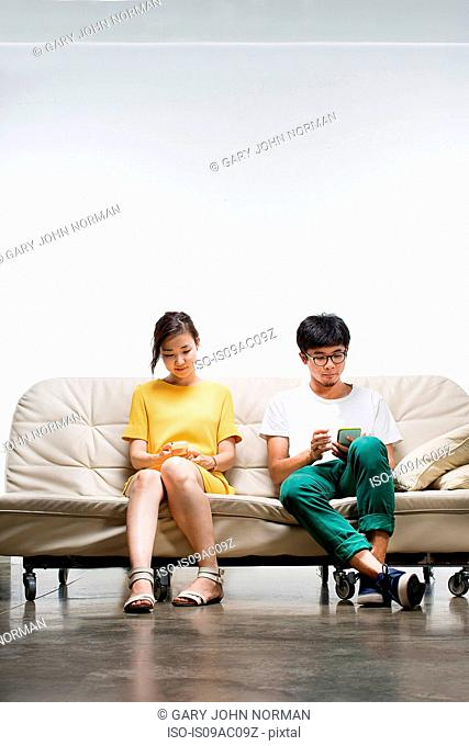 Young adults sitting on sofa using smartphone