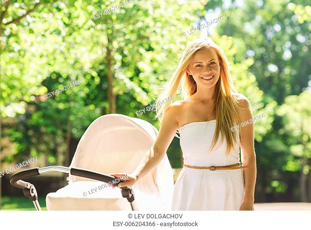 family, child and parenthood concept - happy mother with stroller in park