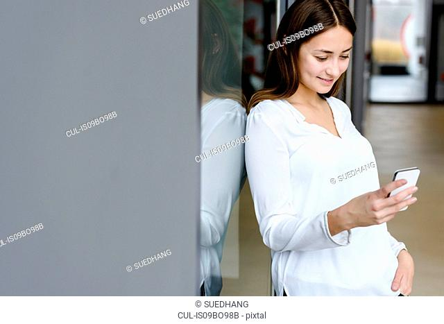 Woman leaning on glass wall using cellphone