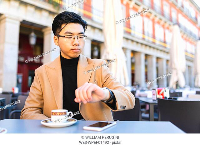 Spain, Madrid, young man checking the time in a cafe at Plaza Mayor