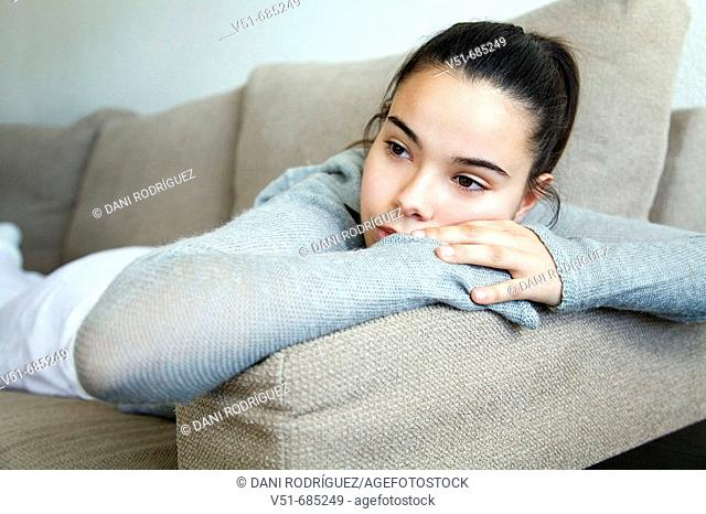 Teenage girl lying on the couch daydreaming