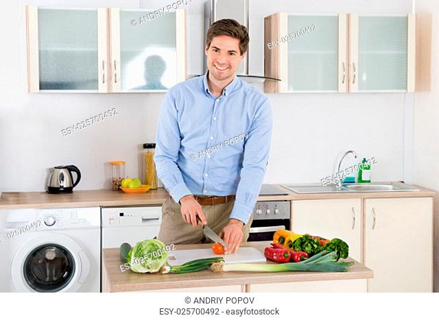 Young Man Smiling While Chopping Vegetables In Kitchen