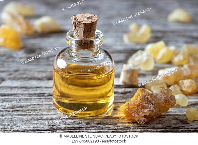 A bottle of essential oil with frankincense resin crystals on a wooden table