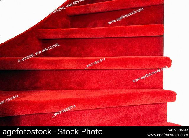 Red carpet on white wooden stairs in a home, close-up luxury modern interior colorful
