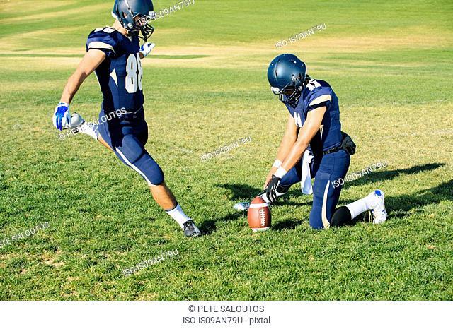 Teenage american footballers kick training on pitch