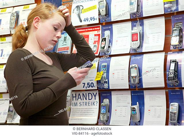 Young woman looking at mobile phones of various manufacturers in a shop. - BONN, GERMANY, 14/02/2005