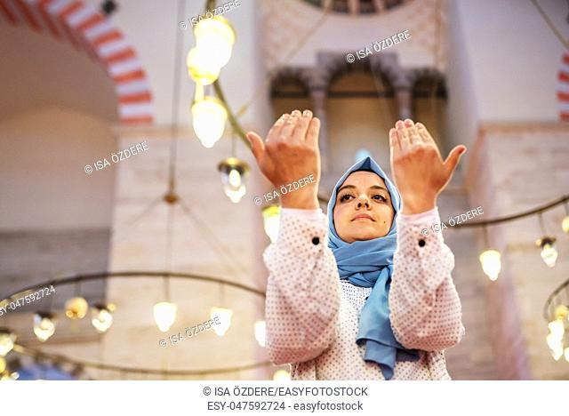 Muslim woman in headscarf and hijab prays with her hands up in air with mosque on background. Religion praying concept