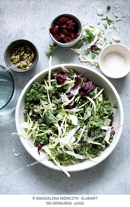 Overhead view of salad leaves in bowl with accompaniments