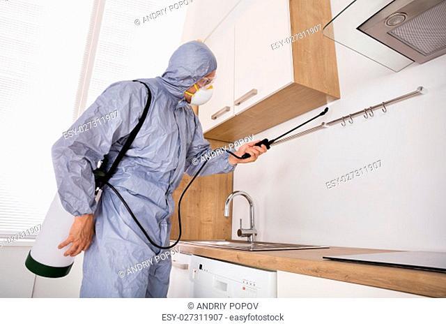 Pest Control Worker In Workwear Spraying Pesticide With Sprayer In Kitchen
