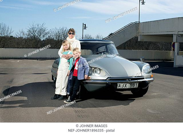 Parents with two children in front of vintage car