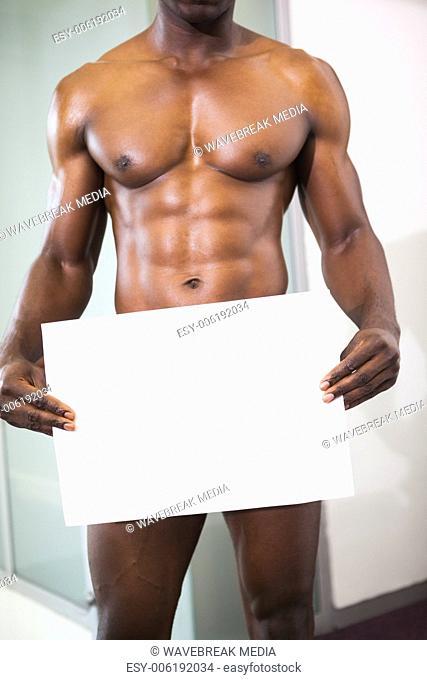 Muscular man holding blank board
