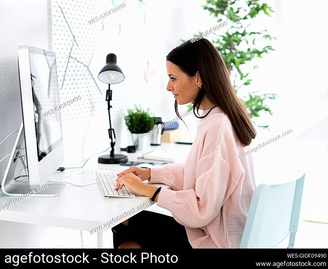 Young female influencer using computer at home