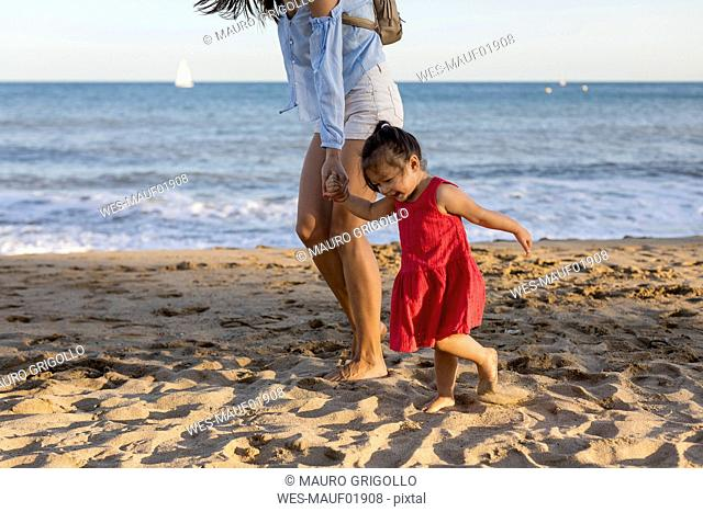 Mother and little daughter walking on the beach, holding hands