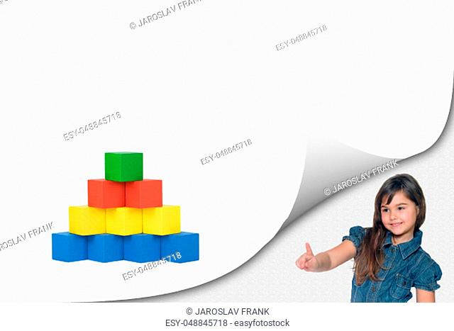 Education concept. Cute tanned little girl standing in an exposed corner is pointing at a blank white page with curl effect with a pyramid created from colorful...