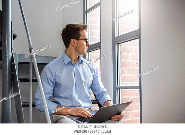 Young businessman using laptop on stairs