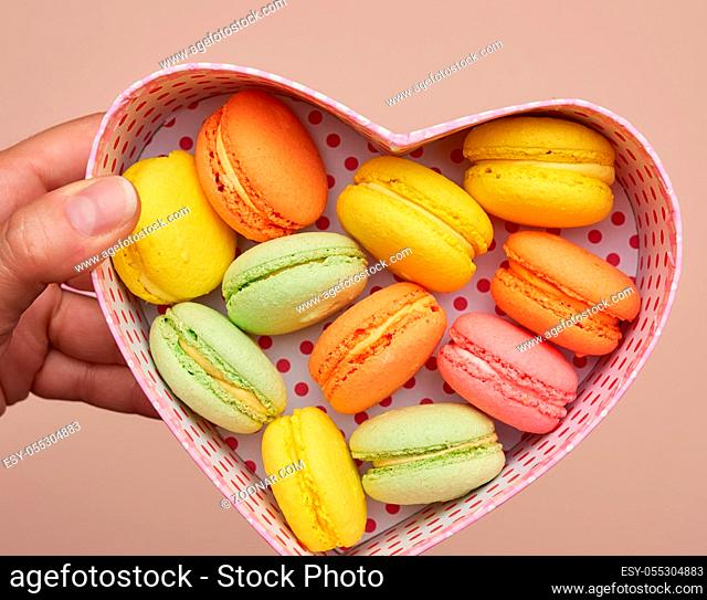 round baked multicolored macarons lie in a pink cardboard box in the shape of a heart, top view
