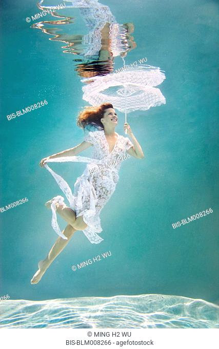 Caucasian woman in elegant dress with parasol under water
