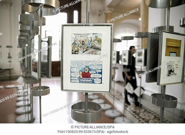 """20 August 2019, Berlin: A visitor looks at postcards exhibited in the anniversary exhibition """"""""More than words"""""""" in the Museum of Communication"""