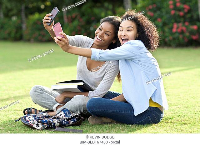Black women taking selfies in park