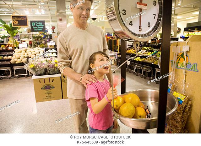 dad and daughter weighing fruit in supermarket