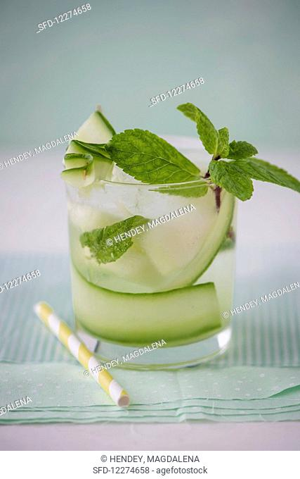 Cucumber and melon water with fresh mint in a glass, close up