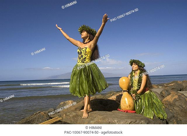 Two hula dancers in traditional outfits on rocky shore, one dancing while the other holds ipu