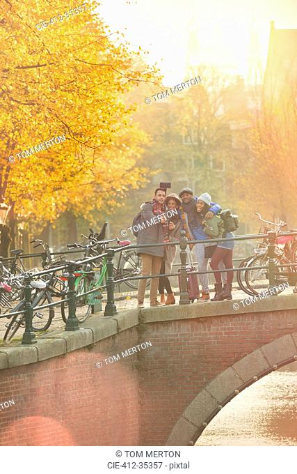 Friends taking selfie with selfie stick on autumn bridge over canal in Amsterdam