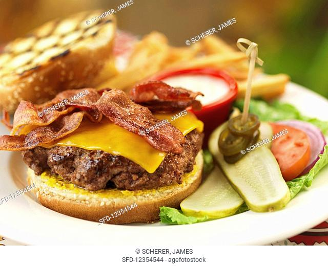 A bacon cheeseburger with salad and fries
