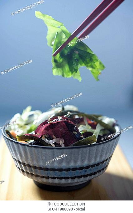 Asian seaweed salad in a bowl with chopsticks