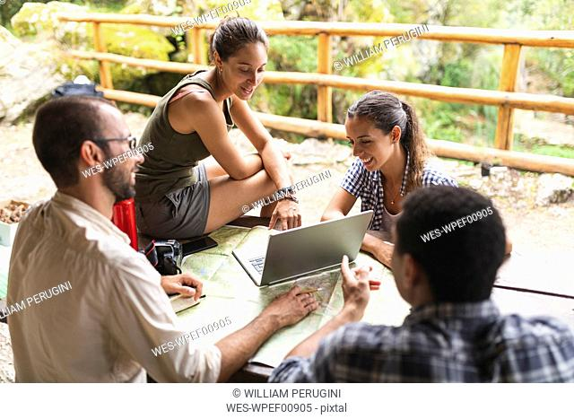 Group of hikers sitting together planning a hiking route using map and laptop