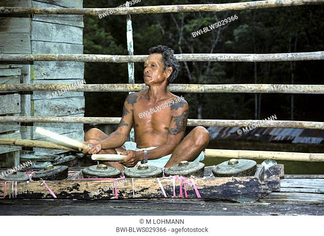 man with Gamelan in the longhouse Bunu of the Dayak Iban, Malaysia, Sarawak
