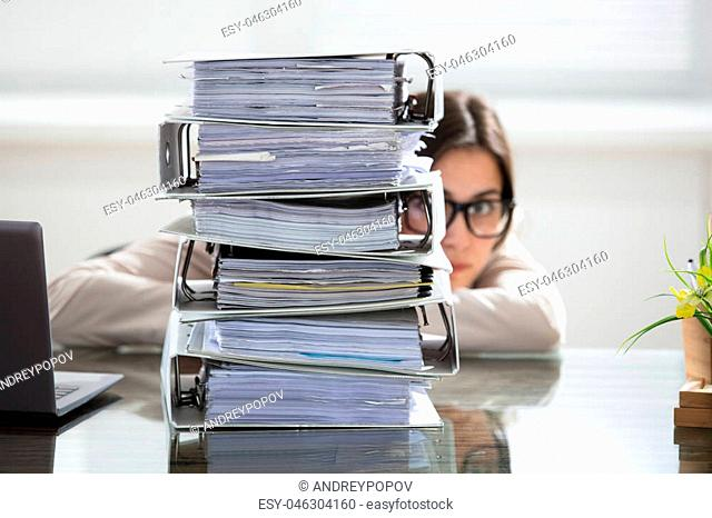 Close-up Of A Businesswoman Hiding Behind The Stack Of Folders On Desk At Workplace