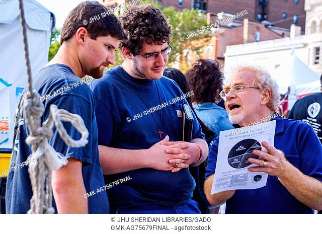 An older man with glasses reads from a flyer about income taxes to two young men wearing crosses and holding bibles, during Baltimore Book Festival, Baltimore