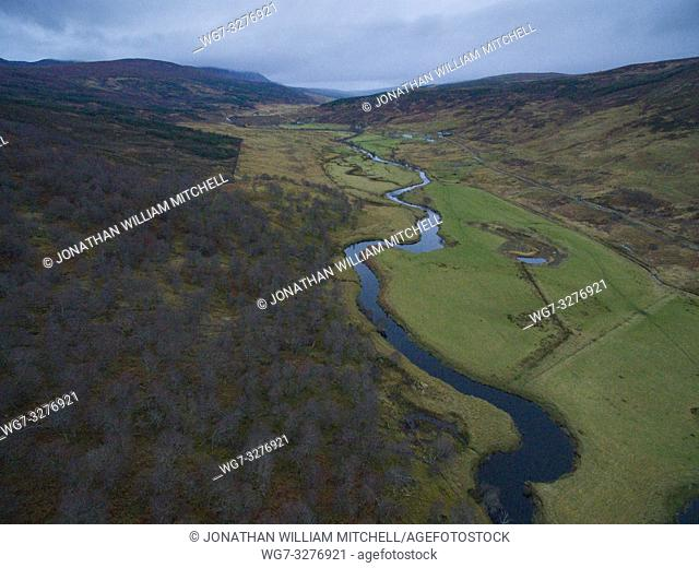 Aerial drone image of the Amat Forest at Strath Cauileannach a tributary of the River Carron in Easter Ross / Sutherland Scotland UK the peak of Carn Salachaidh...