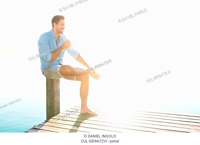 Young man sitting on lake pier drinking coffee, Woerthsee, Bavaria, Germany