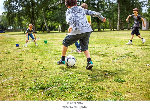 Schoolboys playing soccer at playground