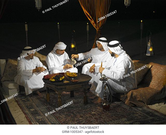 Ramadan: Arab men sitting in Arabian tent for Iftar (fast-breaking meal after sunset)