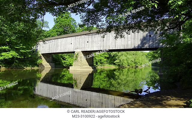 An old wooden covered bridge surrounded by summer foliage, Pennsylvania, USA