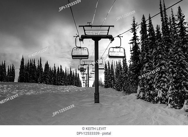 Chair lift at a ski resort in winter; Sun Peaks, British Columbia, Canada