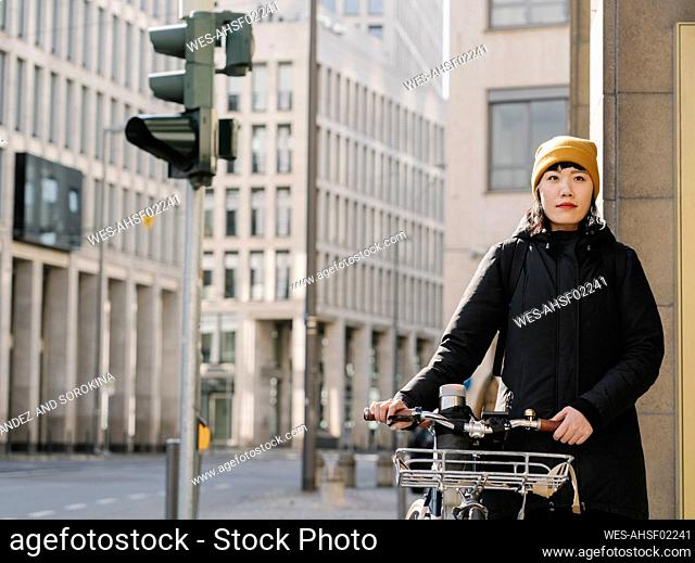 Woman with bicycle in the city, Frankfurt, Germany