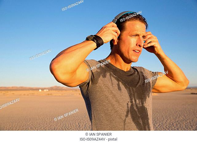 Man training, putting on headphones on dry lake bed, El Mirage, California, USA
