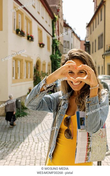Germany, Rothenburg ob der Tauber, portrait of happy woman shaping heart with her fingers