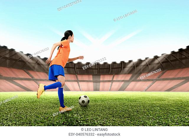 Image of asian female footballer kicking the ball on the field