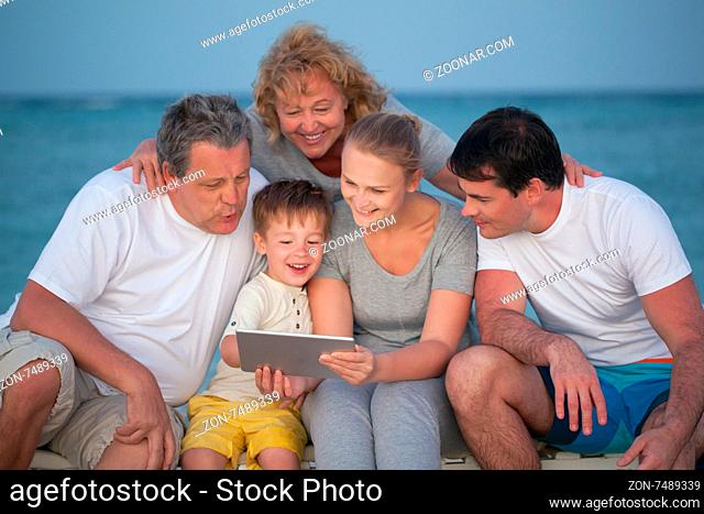 Child using tablet computer and his big family including parents and grandparents looking at screen. They sitting at the seaside