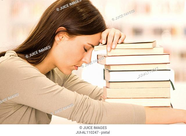 Young student leaning head against stack of textbooks in library