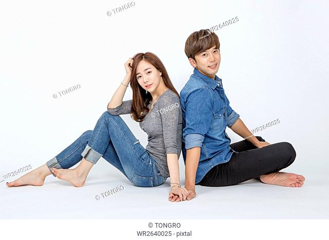 Side view of young smiling couple sitting back to back