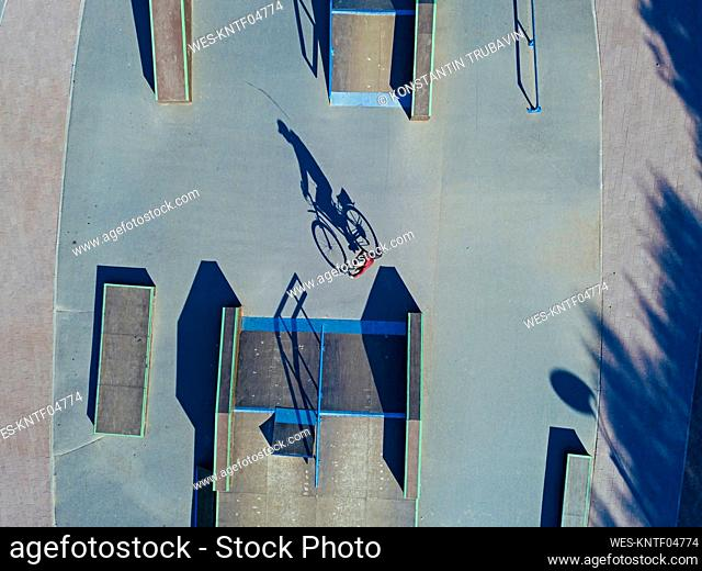 Man cycling in skate park, aerial view